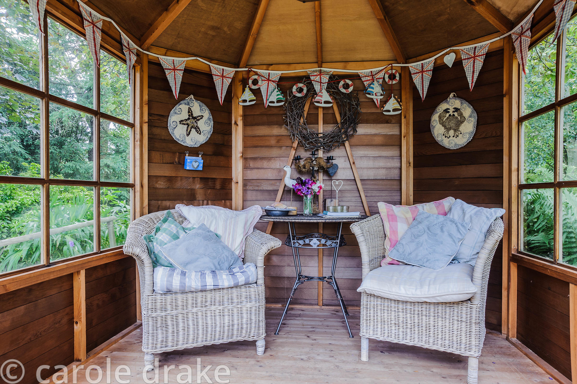 Summerhouse decorated with seaside themed objects including starfish, boats, birds, shells and bunting.