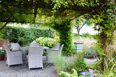 Rose covered arbour over a dining area in a rural garden in Nottinghamshire in September, with bubble millstone water feature...