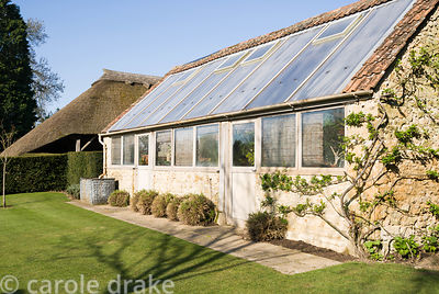 Greenhouse built against outside of walled kitchen garden. Melplash Court, Bridport, Dorset, UK