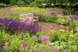 Wooden seats in The Perennial Meadow, and the Victorian Conservatory, at Scampston Hall Walled Garden, North Yorkshire, desig...