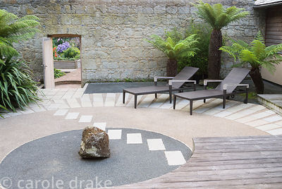 Japanese style courtyard garden beside the house features contrasting surfaces, tree ferns and outdoor furniture by Gloster. ...