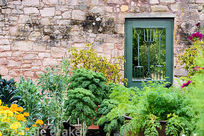 A door into the Walled Garden incorporating old hand forks at Broadwoodside, Gifford, East Lothian in September