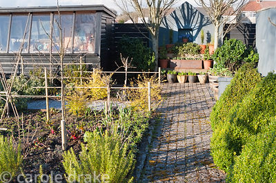 A path of stone setts in a formal kitchen garden runs between clipped box and beds of herbs and veg, toward display staging a...