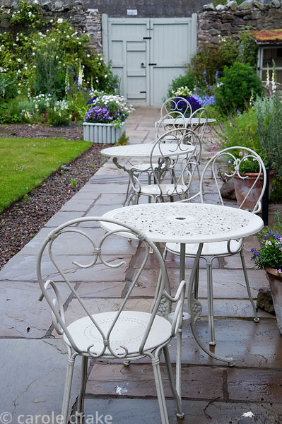 Metal chairs and tables on stone terrace beside the house. Mindrum, nr Cornhill on Tweed, Northumberland, UK