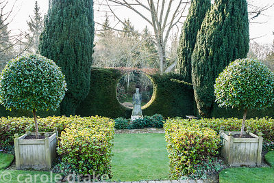 Statue of oriental priest is framed by a circlur window cut into a yew hedge that supports a honeysuckle, viewed from top of ...
