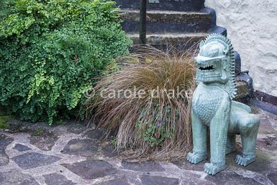 Guardian lion beside bronze carex and Adiantum capillus-veneris at Barn House, Gloucestershire in September
