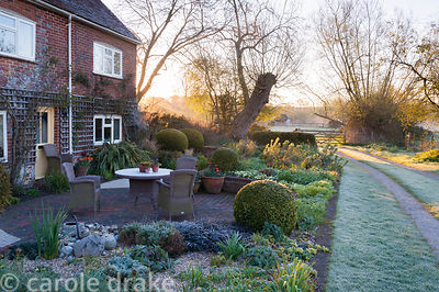 Front garden with sunken seating area framed with brick edged raised beds, and year round structure provided by clipped box s...