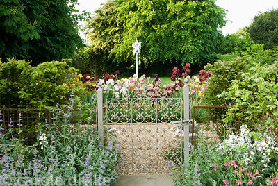 White dovecot seen beyond bed of irises and decorative wrought iron gate. Old Rectory, Kingston, Isle of Wight, Hants, UK