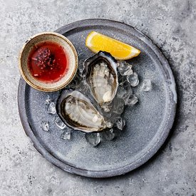 Fresh open Oysters Fin de Claire on ice and Mignonette sauce on gray background