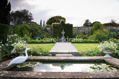 Raised pond in the White Garden at Bourton House, Moreton-in-Marsh in August with pots of Argyranthemum 'Starlight' at each c...
