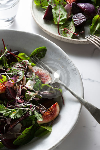 A salad of roasted beetroot, purple carrots and purple onions, with fresh figs, mixed leaves and microherbs, dotted with feta...