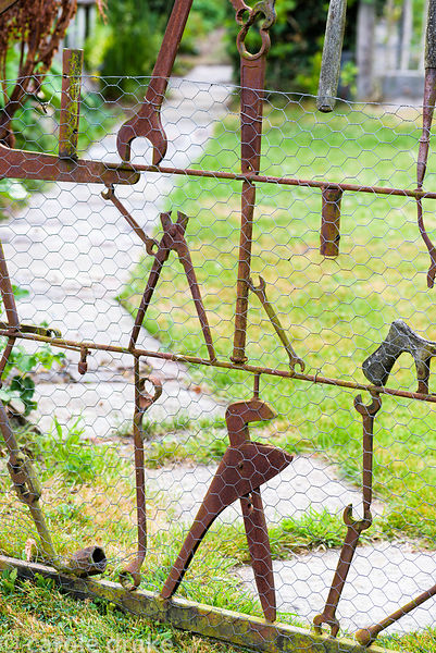 Decorative gates made using old rusty tools including spanners and wrenches at Five Oaks Cottage garden in July