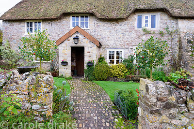 Cobble path leads to the front door of the thatched cottage between standard hollies hung with Christmas decorations