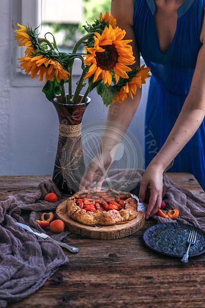 Woman serving rustic apricot galette on a wooden table