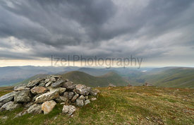 Dark clouds gather over the mountains in the evening from the summit of Rampsgill Head with Rest Dodd, The Nab and Martindale...