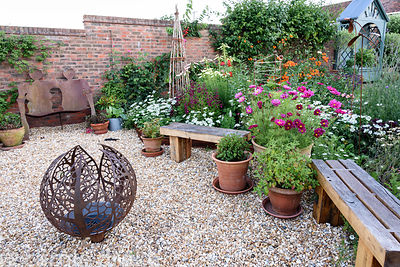 Gravelled area with decorative fire sphere amidst cosmos, penstemons and Orlaya grandiflora at Malthouse Farm, Hassocks, Sussex