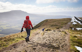 A hiker walking down from the summit of Whernside, part of the T