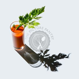 Carrot juice with celery on gray background