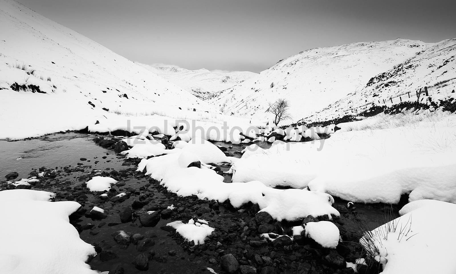 A black and white image of a winter snowy Lake District scene of Hayeswater Gill near Hartsop in the Lake District.