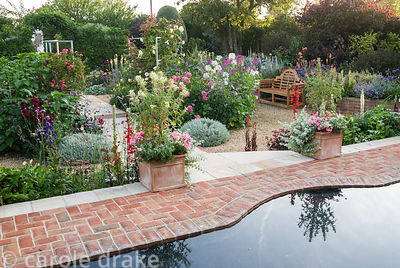 Reflecting pool in front of the summerhouse with views down into the sunken garden, a mass of colourful perennials and annual...