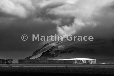 Black & White image of large tabular iceberg with dark sky over land, Weddell Sea, Antarctica