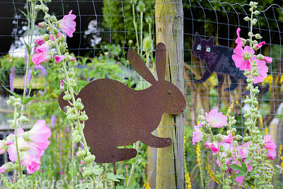 Flat metal animal shapes attached to a wire fence amongst hollyhock flowers at Five Oaks Cottage in July