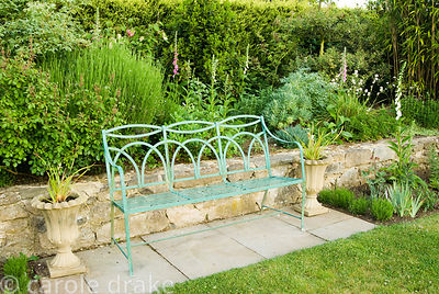 Metal bench at the end of the crab apple lawn, surrounded by foxgloves, lavenders, roses and irises. Old Rectory, Kingston, I...
