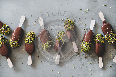 Chocolate glazed ice cream pops over grey background, top view