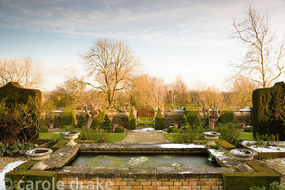 A rectangular pond with box 'corners' in the white garden at Bourton House in the Cotswolds on a snowy January day