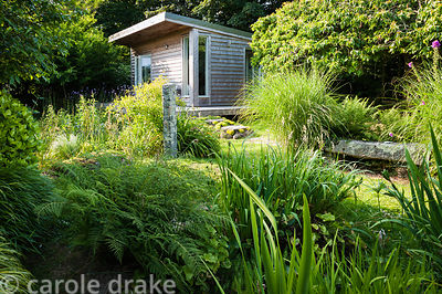 Sara's garden office amongst large clumps of miscanthus, ferns and irises. The 'Garten' Garden, Lower Treculliacks Farm, Falm...