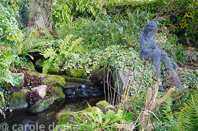 Chicken wire girl by Derek Kinzett sits beside a small pond in the back garden surrounded by foliage plants including ivies, ...