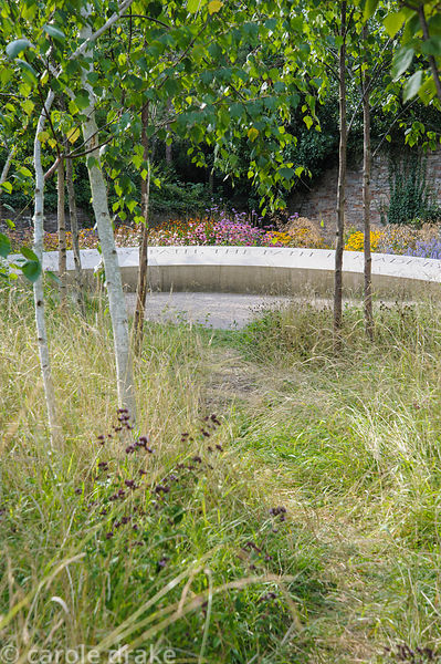The Garden of Reflection features a grove of 85 silver birch trees, a 40' long stone seat inscribed with the words 'Wanderer,...