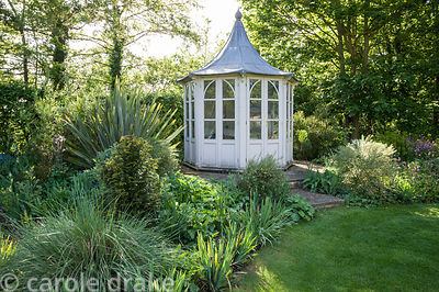 Summerhouse framed by borders planted with broom, yew and grasses.