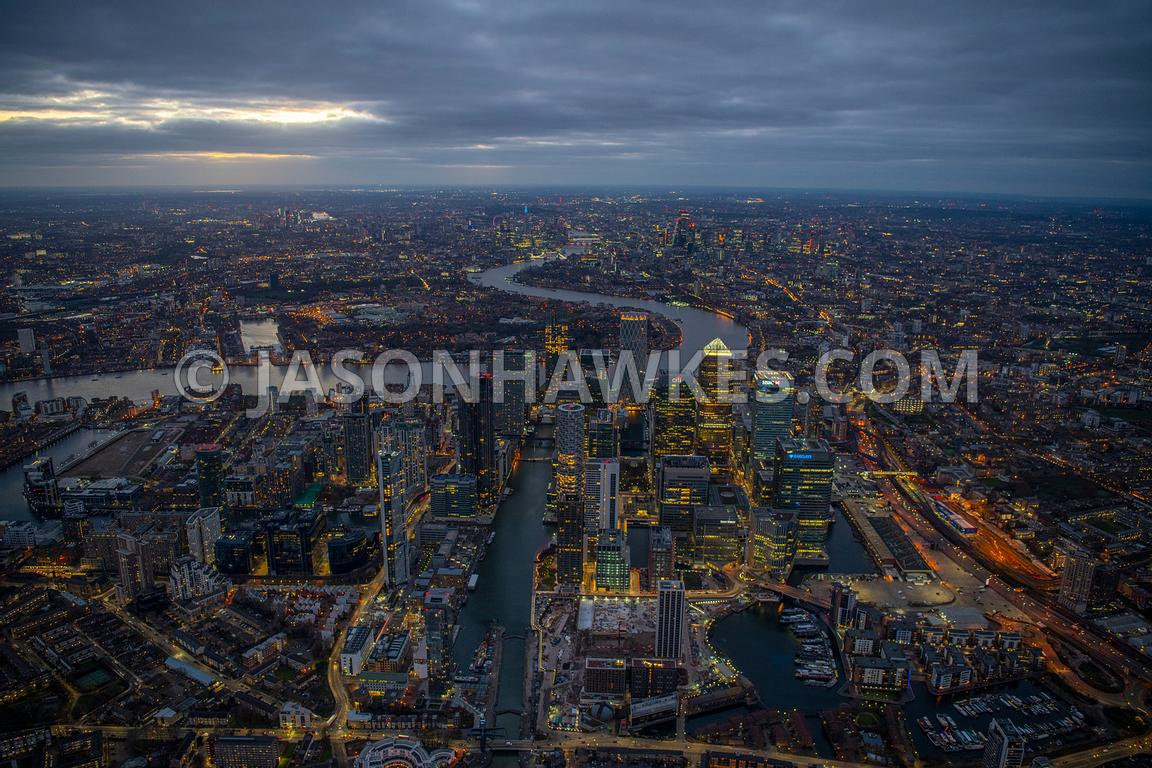 Helicopter aerial view of Canary Wharf, Isle of Dogs, London at dusk.