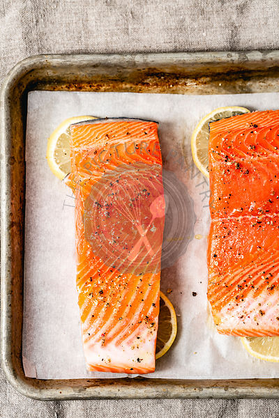 Fresh Salmon in a baking tray, ready for the oven, with slices of lemon.