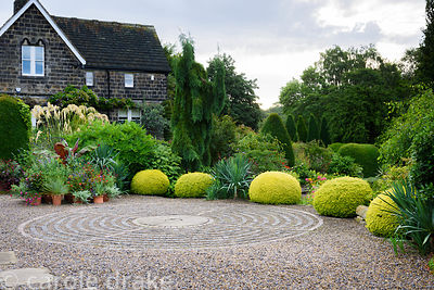 Circular pavement maze created with stone setts in gravel in the driveway, surrounded by clipped yew spheres, yuccas and othe...