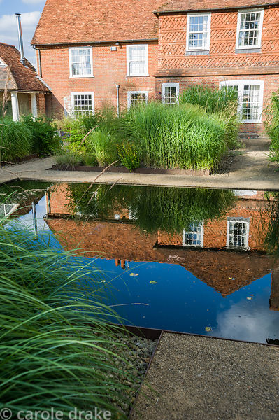 At the centre of the minimalist front garden, designed by Christopher Bradley-Hole is a still pool surrounded by tall miscant...