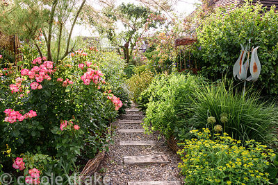 A gravel path set with sections of weathered railway sleeper passes between lushly planted borders edged with woven willow an...