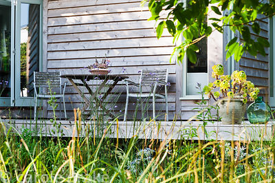 Table and chairs on the decking around Sara's garden office with pot of aeonium nearby. The 'Garten' Garden, Lower Treculliac...