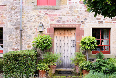 Front door in the Upper Courtyard framed by standard bays, sarcococca, Mahonia 'Soft Caress, ferns and clipped box at Broadwo...