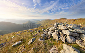 The summit cairn of Rampsgill head at sunset with views of Ramps Gill and Martindale Common in the evening sun in the Lake Di...