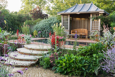 Summerhouse with reflecting pool surrounded by brightly coloured perennials including Lobelia cardinalis, cleomes, plectranth...