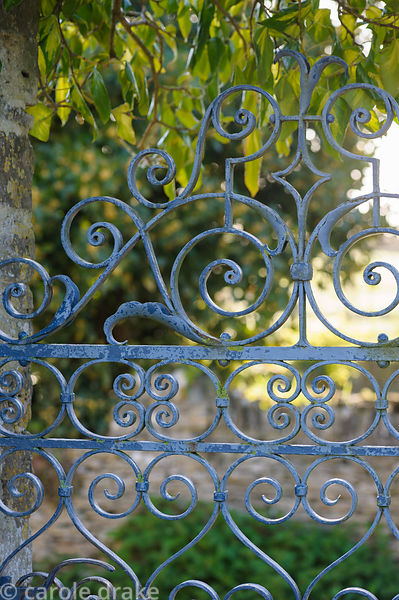 Curlicued painted metal gate between the garden and adjoining track beyond which is the potager and vegetable garden at Barns...