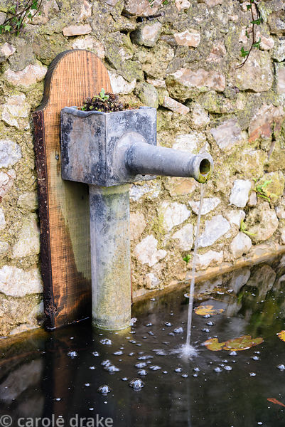 Decorative water spout empties into an old drinking trough