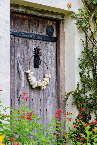 Pebbles and shells sstrung onto a metal arabesque hanging on a door at Five Oaks Cottage in July