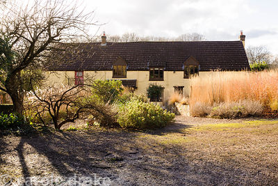 Barn House framed in winter by the bleached stems of Calamagrostis x acutiflora 'Karl Foerster' and colourful winter stems of...