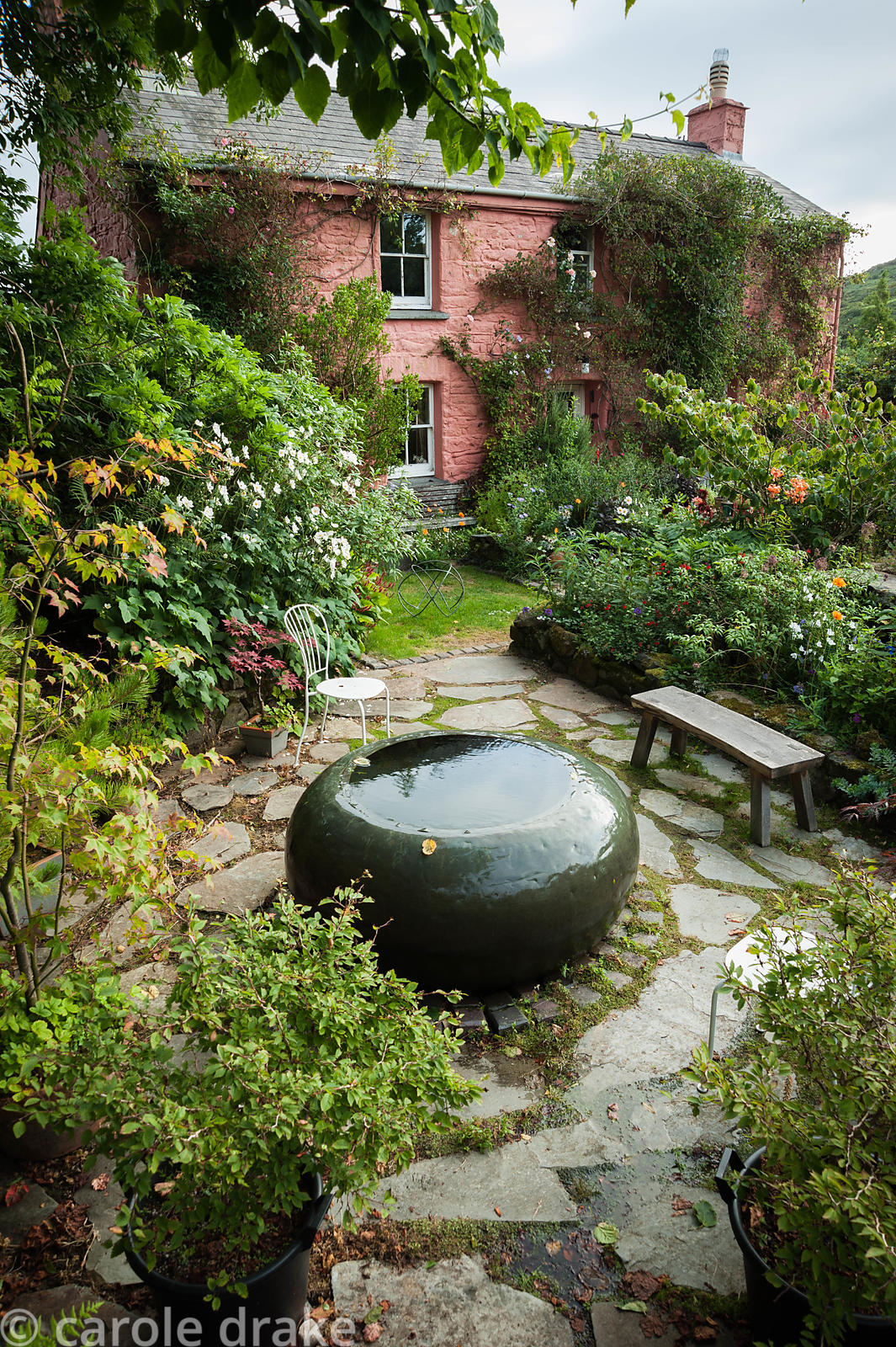 Front garden features a large copper water feature, formerly part of a whisky still, surrounded by lush planting including sa...