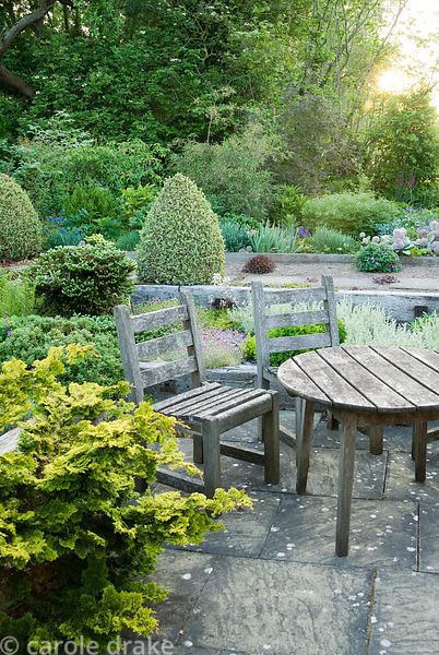 Seating area with raised beds behind constructed with weathered railway sleepers. Two lines of Buxus sempervirens 'Elegantiss...