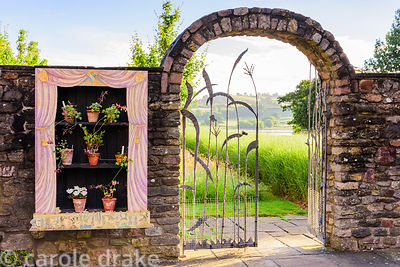 Auricula theatre displaying scented leaved pelargoniums beside a gate leading to an are of long grasses with Blagdon Lake bey...