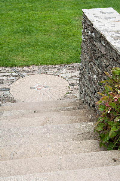 Millstone set into paving on the terrace. Coleton Fishacre, Kingswear, Devon, UK